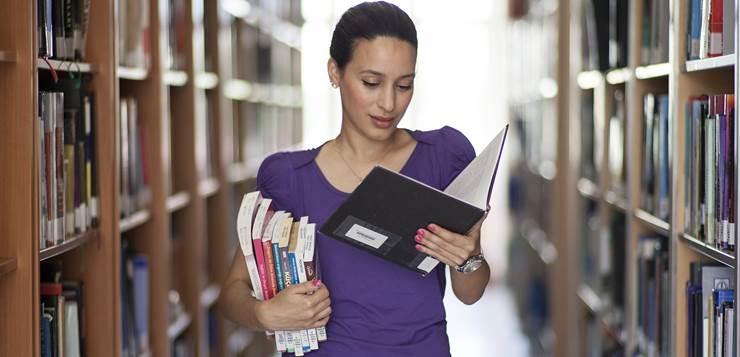 devojka čita knjige u biblioteci