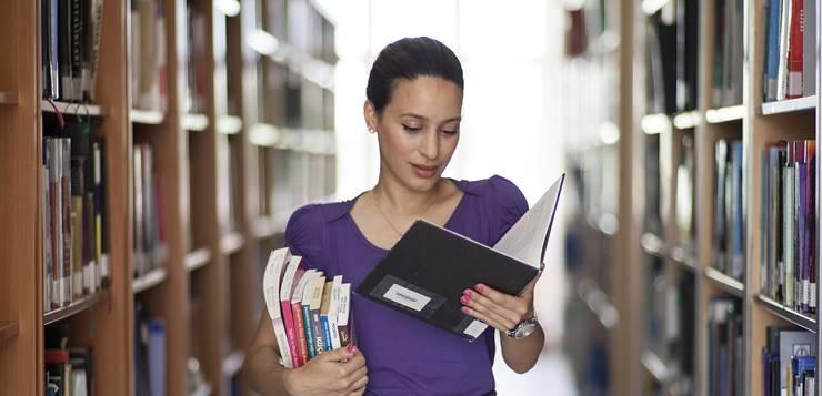 Devojka koja čita u biblioteci