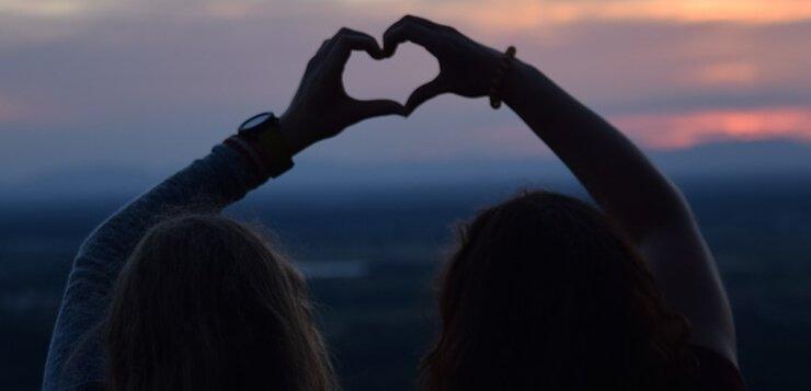 Dve devojke koje prstima prave srce