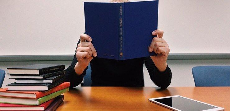 student čita knjigu za stolom