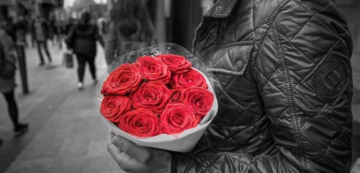 Momak koji nosi crvene ruže