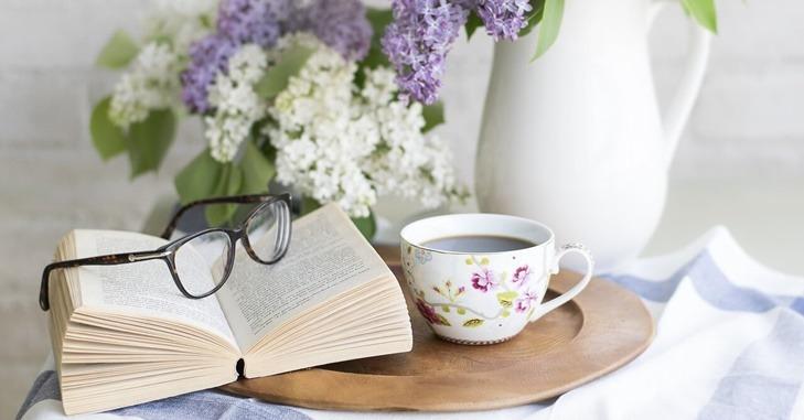 Naočare naslonjene na knjgu na stočiću sa kafom
