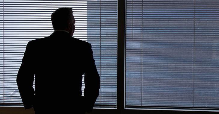 Biznismen gleda kroz prozor od kancelarije,