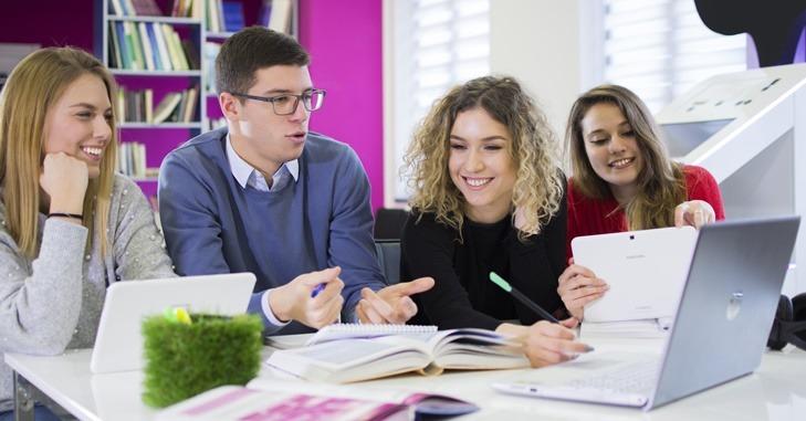 mladi ljud na sede za stolom i rade