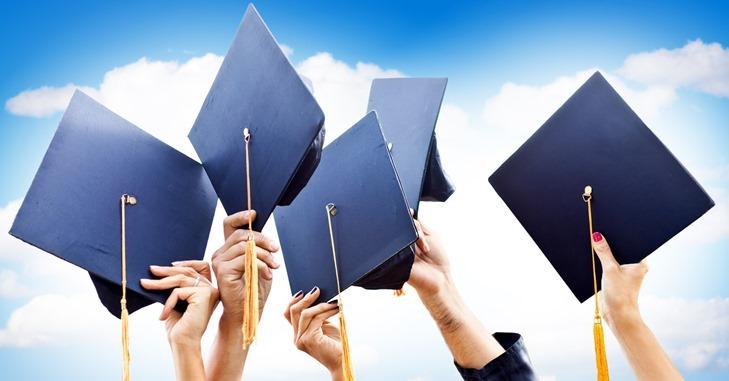 Plave kape koje diplomci drže u rukama