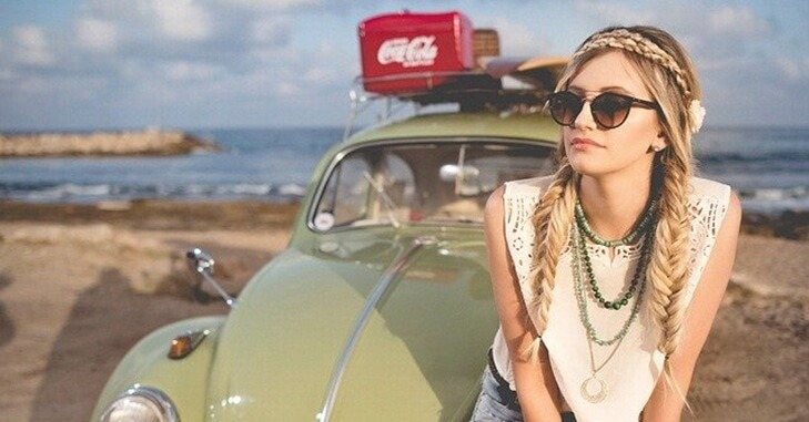 Devojka sa naočarima sedi na automobilu