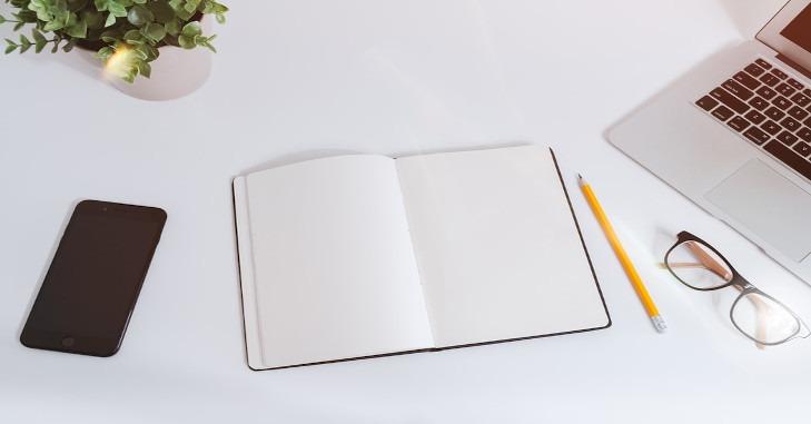 Skveska za pisanje na stolu pored laptopa