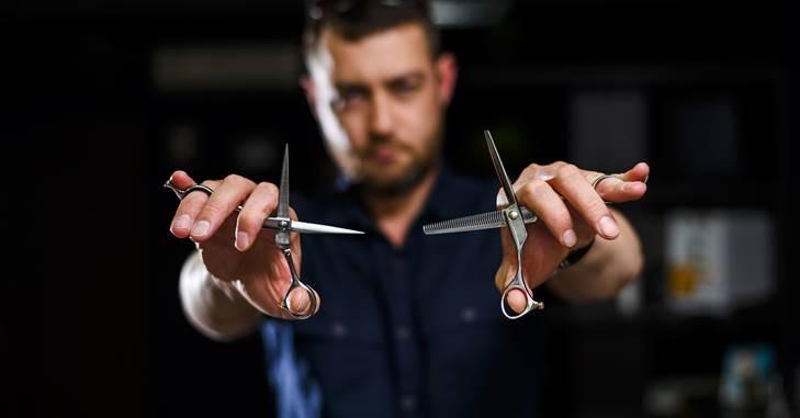 Muškarac koji drži makaze za šišanje