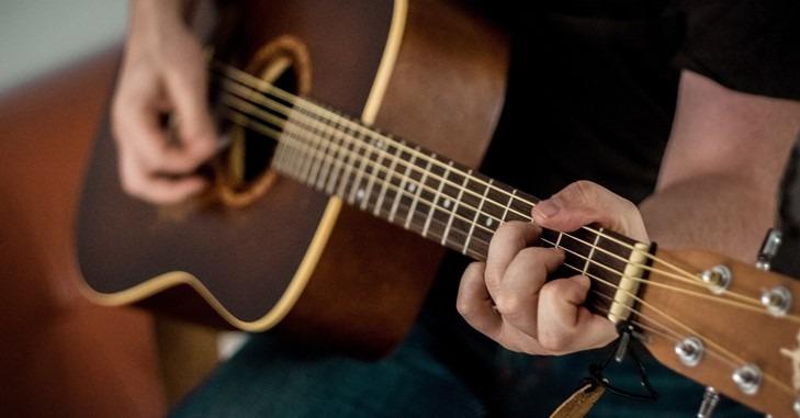 Momak koji svira gitaru u krilu