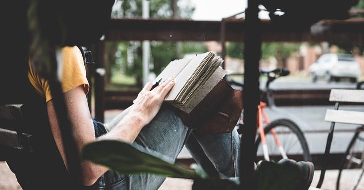 Devojka na stolici čita knjigu