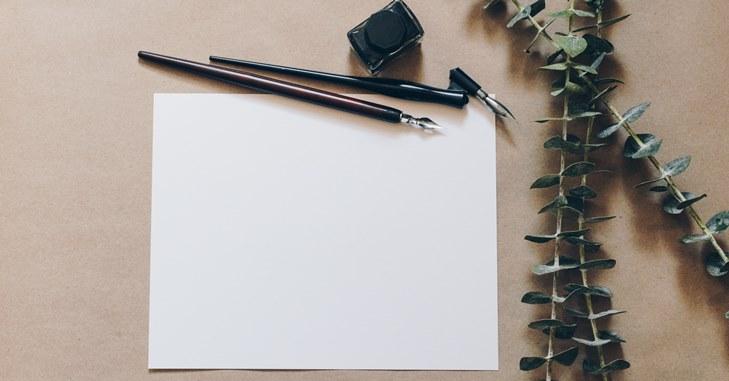Penkalo i beli papir na stolu
