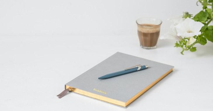 Siva sveska na kojoj se nalazi plava olovka