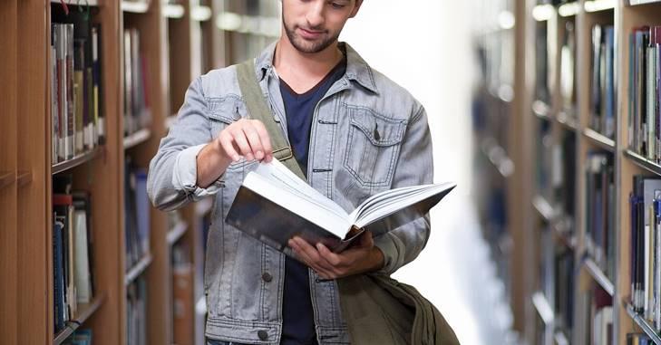 Čovek koji stoji i čita knjigu u biblioteci