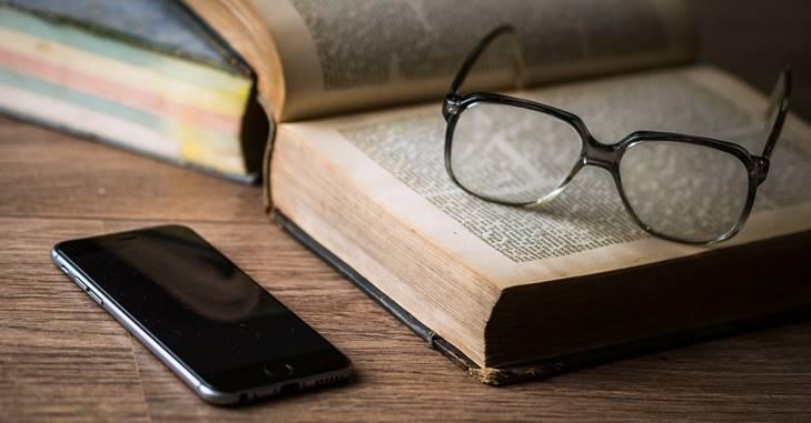 Otvorena knjiga na kojoj se nalaze naočare