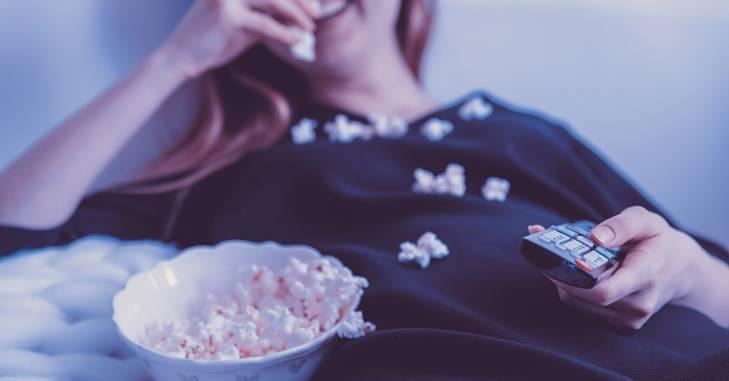 Devojka koja leži i jede kokice iz činije