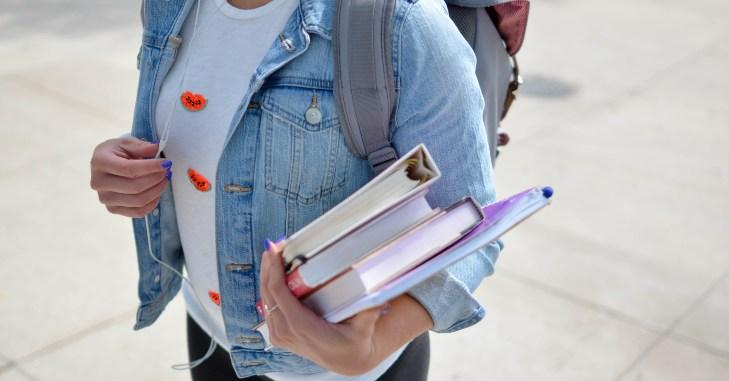 Devojka koja drži knjige u ruci