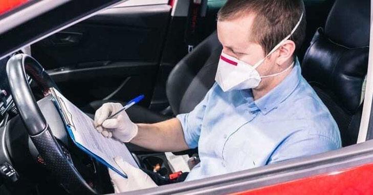 Čovek u kolima sa maskom polaže vozački ispit