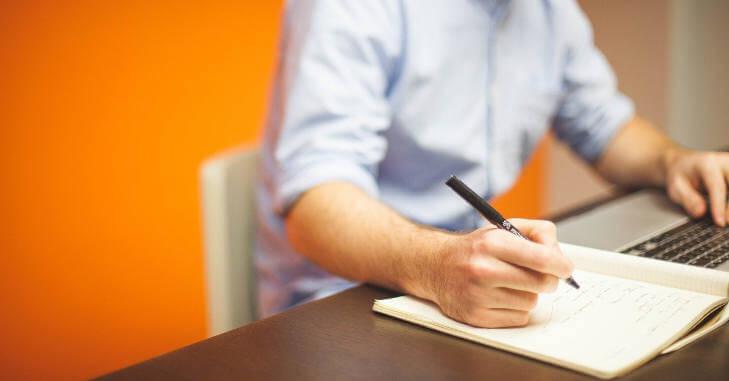 Muškarac za računarom pored kog se nalazi i sveska u kojoj piše