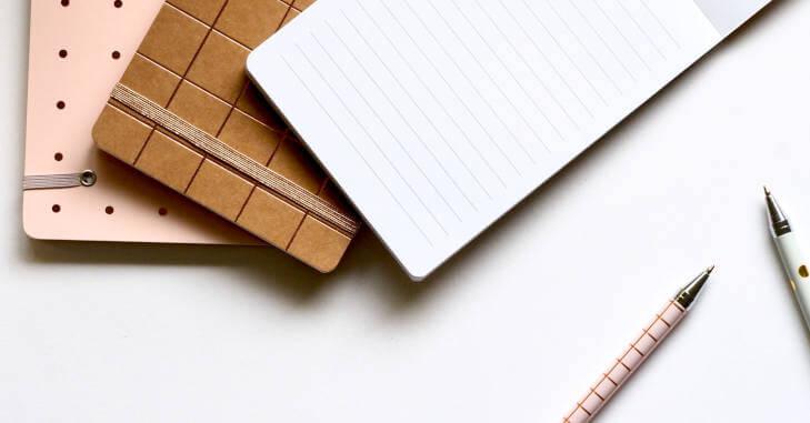 Tri notesa različitih boja i dve olovke na beloj pozadini