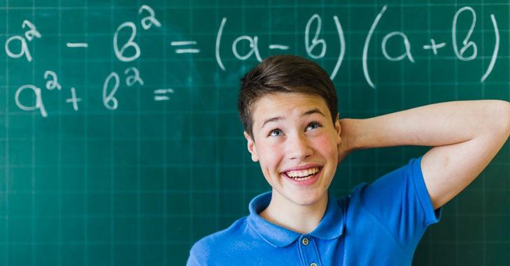Dečak ispred table u školi na kojoj se nalazi matematička jednačina