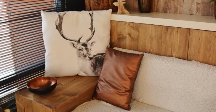 Enterijer u kom je prikazan drveni nameštaj i jastuci sa slikom jelena