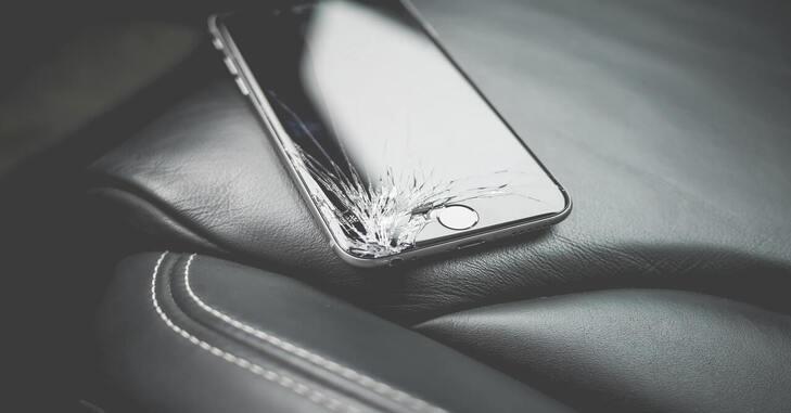 crni teleofn sa razbijenim ekranom na sedištu automobila