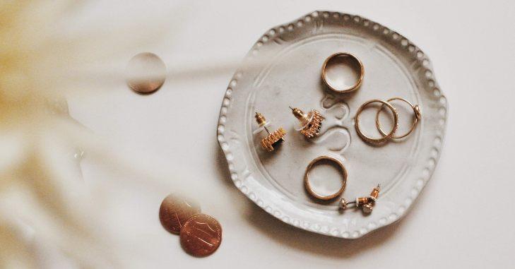 Zlatno prstenje i minđuše na beloj podlozi
