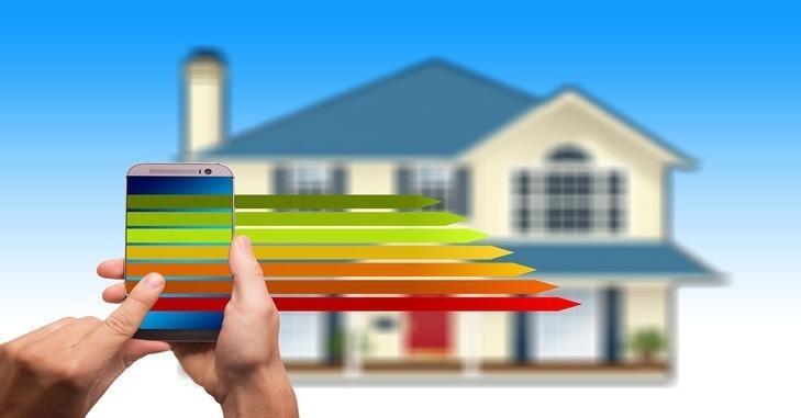grafički prikaz pasivne kuće i ruke u kojoj je pametan telefon