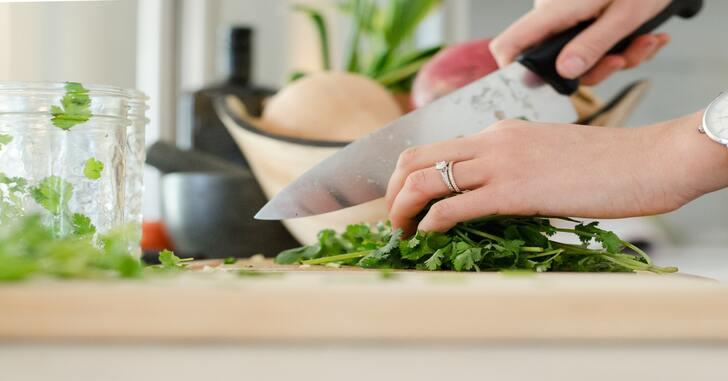 prikaz ruke koja nožem secka zelenu salatu