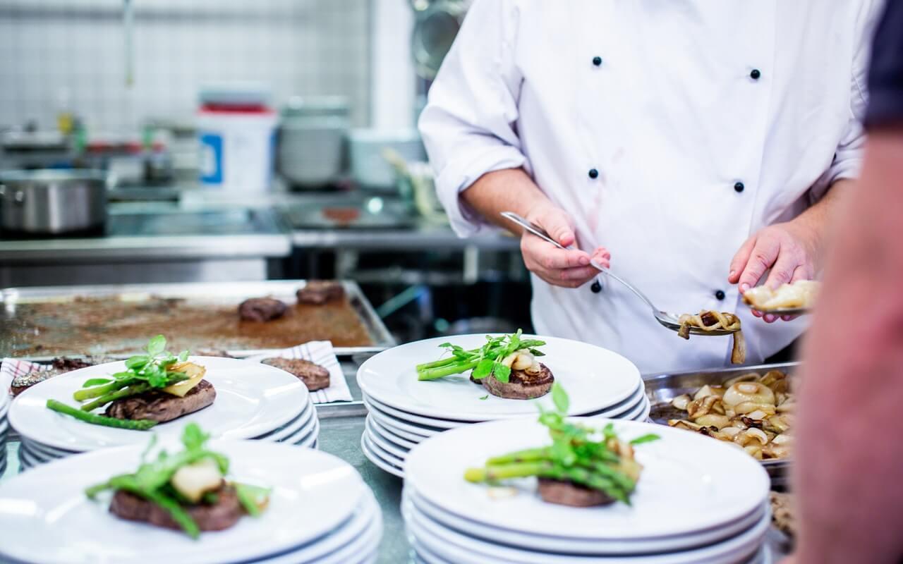 kuvar u beloj uniformi priprema hranu u restoranskoj kuhinji