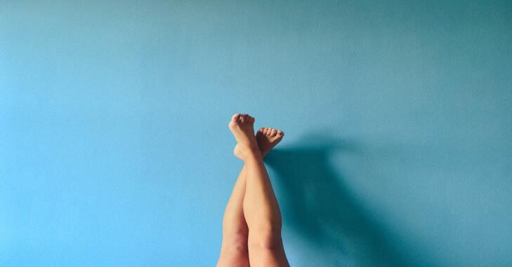 prikaz ženskih nogu koje su naslonjene na plavi zid