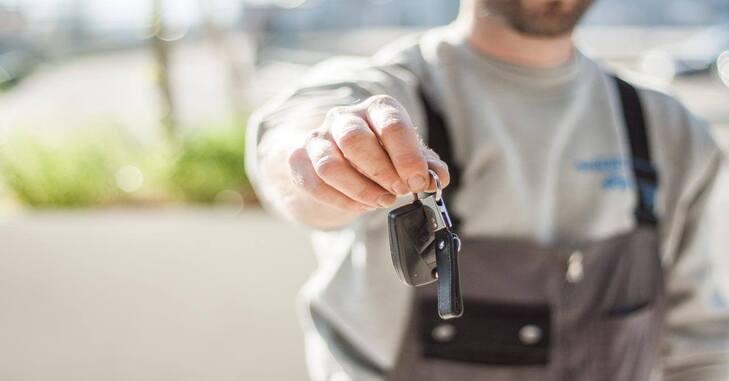 prikaz muškarca koji drži ključeve od kola