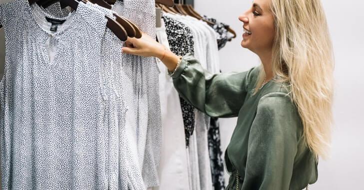 devojka koja razgleda odeću u radnji
